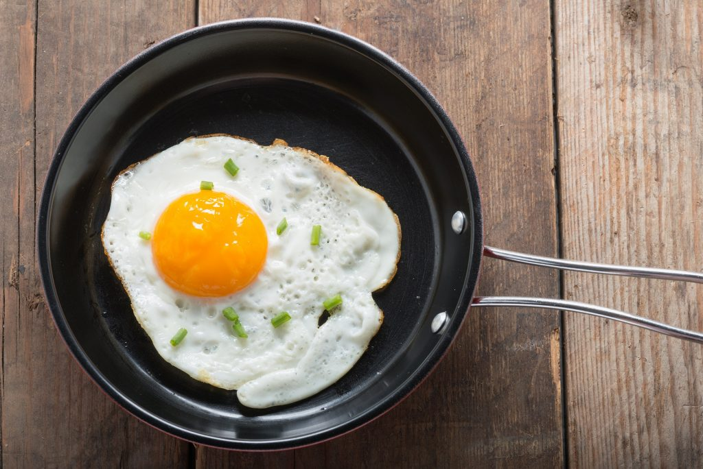 Fried,eggs,in,pan,with,handle,on,table,,top,view